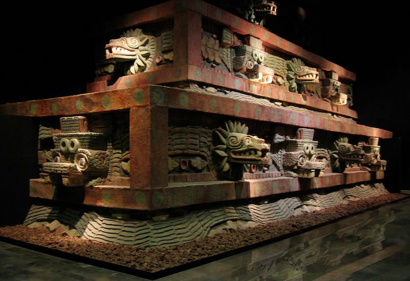 Teotihuacan style architecture displaying decorative ornamentation made of obsidian and shell inlaid into a painted cantera surface set upon a tezontle interior